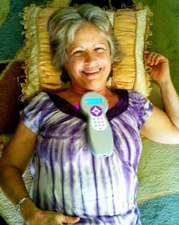 Photo of Joy Gardner lying down while receiving a healing with a Quantum Wave Laser